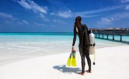 Vrouwelijke scuba-duiker met duikuitrusting op het strand stock afbeeldingen