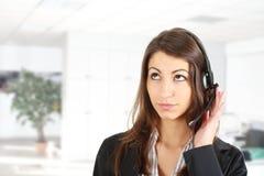 Vrouwelijke secretaresse die over de hoofdtelefoon spreken Royalty-vrije Stock Afbeelding