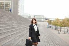 Vrouwelijke secretaresse die zich op treden met zak en hoge gebouwen op achtergrond bevinden Royalty-vrije Stock Foto