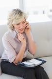 Vrouwelijke secretaresse met agenda terwijl het gebruiken van mobiele telefoon Royalty-vrije Stock Afbeelding