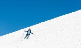 Vrouwelijke skiër die een steile helling aanpakken stock foto's