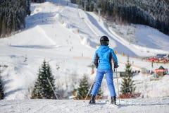 Vrouwelijke skiër op een skihelling bij een zonnige dag stock foto