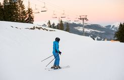 Vrouwelijke skiër op midden van skihelling tegen skiliften royalty-vrije stock fotografie