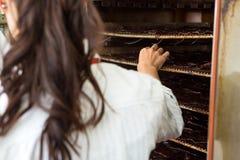 Vrouwelijke Slager Standing By Oven In Shop Stock Afbeeldingen