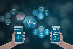 Vrouwelijke smartphone van de handholding om de prijs voor bod, via draadloos netwerk op blauwe bokehachtergrond met veilingspict royalty-vrije stock afbeeldingen