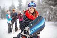 Vrouwelijke snowboardergreep snowboard stock afbeeldingen