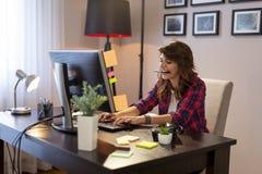 Vrouwelijke IT specialist die in een huisbureau werken stock foto