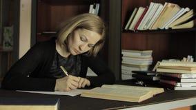 Vrouwelijke spreker die met boeken in een bibliotheek in universiteit werken Vermoeide student die voor examens voorbereidingen t stock footage