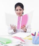 Vrouwelijke stafmedewerker die een dossier bekijkt Stock Afbeelding