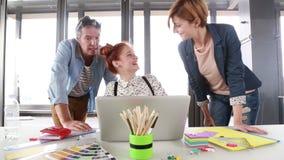 Vrouwelijke stafmedewerker die nieuw project op laptop voorleggen aan directeur en collega stock videobeelden
