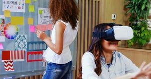 Vrouwelijke stafmedewerker virtuele werkelijkheidshoofdtelefoon met behulp van en collega die kleverige nota's bekijken stock videobeelden
