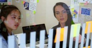 Vrouwelijke stafmedewerkers die over een kleverige nota 4k bespreken stock video