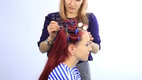 Vrouwelijke stilist die perfect kapsel met grote krullen voor jonge roodharigevrouw cre?ren stock footage