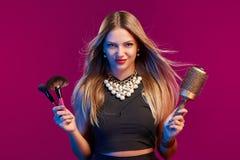 Vrouwelijke stilist die zich met hairdresser& x27 bevinden; s toebehoren en make-upborstels royalty-vrije stock foto