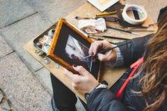 Vrouwelijke straatkunstenaar die een scène in Sevilla schilderen stock afbeelding