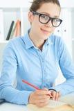 Vrouwelijke student bij werkplaats met boek Stock Afbeeldingen