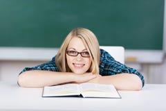 Vrouwelijke Student With Book Leaning op Bureau in Klaslokaal stock afbeeldingen