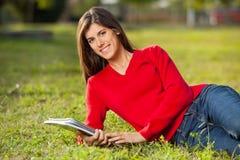 Vrouwelijke Student With Books Relaxing op Gras bij royalty-vrije stock foto's
