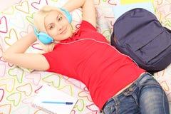 Vrouwelijke student die in bed liggen die aan muziek luisteren royalty-vrije stock foto