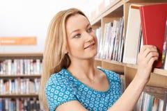 Vrouwelijke Student die in Bibliotheek bestuderen stock foto