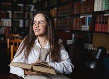Vrouwelijke Student die in Bibliotheek bestuderen stock foto's