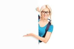 Vrouwelijke student die bij een lege banner tonen Stock Afbeeldingen