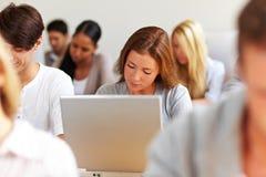 Vrouwelijke student die bij laptop werkt Stock Foto's
