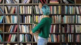 Vrouwelijke student die boek op plank in bibliotheek kiezen stock video