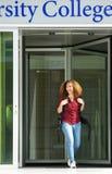 Vrouwelijke student die de universiteitsbouw verlaten Royalty-vrije Stock Fotografie