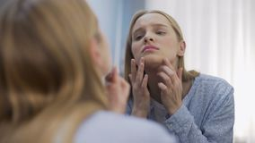 Vrouwelijke student die droevig gezichtsbezinning bekijken in moeilijkheden van de spiegel de jonge leeftijd stock footage