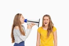 Vrouwelijke student die een luidspreker op een ander meisje met behulp van Royalty-vrije Stock Fotografie