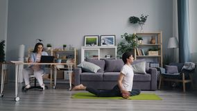 Vrouwelijke student die met laptop werken die wanneer haar echtgenoot die yoga thuis doen bestuderen stock video