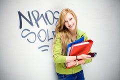 Vrouwelijke student die tegen graffitimuur leunt Stock Fotografie