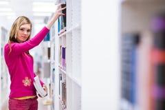 Vrouwelijke student in een bibliotheek Stock Foto's