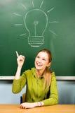 Vrouwelijke student en gloeilamp op bord Stock Afbeeldingen