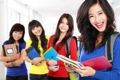 Vrouwelijke student en vrienden die aan camera glimlachen stock afbeeldingen