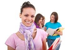 Vrouwelijke student en vrienden in rug Stock Fotografie