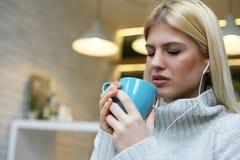 Vrouwelijke student het luisteren muziek en het drinken koffie Stock Foto's
