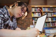 Vrouwelijke student het schrijven nota's in bibliotheek Stock Foto's