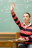 Vrouwelijke student met haar opgeheven hand Stock Foto's