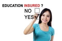 Vrouwelijke student met tekst van verzekerd onderwijs Stock Afbeelding