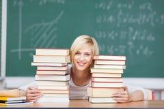 Vrouwelijke Student With Stacked Books bij Bureau Royalty-vrije Stock Fotografie