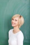 Vrouwelijke Student Standing Against Chalkboard stock foto's