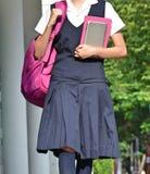 Vrouwelijke Student With Uniform Walking aan School royalty-vrije stock afbeeldingen