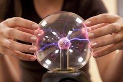 Vrouwelijke student wat betreft een plasmabal. royalty-vrije stock afbeelding