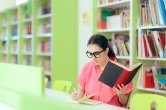 Vrouwelijke Student Writing een Pogingstaak in Schoolbibliotheek stock afbeelding