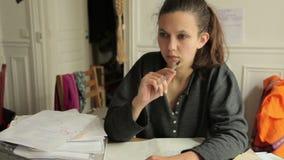 Vrouwelijke student Writing en het denken stock video