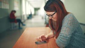 Vrouwelijke studente die nota's van het letten van op taak op een smartphone bij de universitaire universiteit nemen Vrouwenzitti stock footage