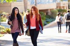 Vrouwelijke Studenten die in openlucht op Universitaire Campus lopen Royalty-vrije Stock Afbeeldingen