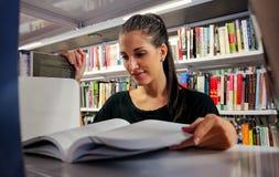 Vrouwelijke studentenlezing in de Bibliotheek van de Universiteitscampus royalty-vrije stock foto